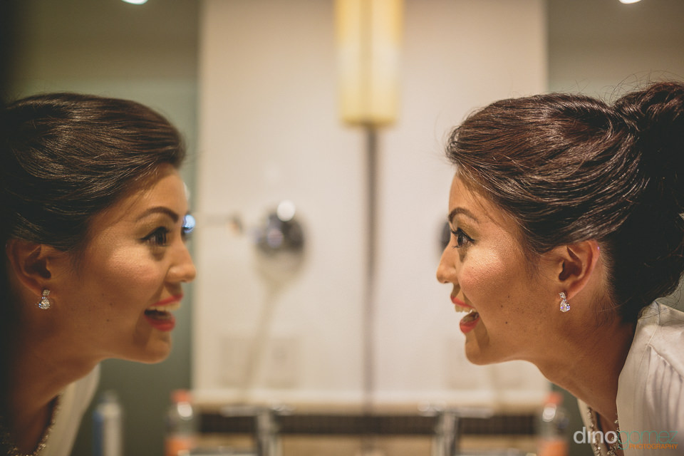bride smiles and looks at reflection in mirror on wedding day in