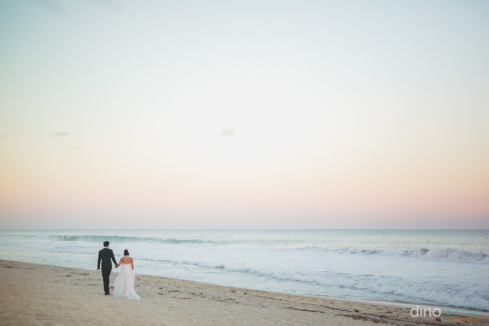 sunset walk on the beach for young newlyweds in cabo san lucas