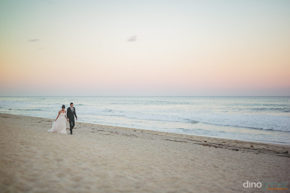 romantic walk on the beach for newlyweds at sunset in photo take