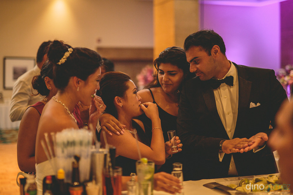 wedding guests drink tequila with lime at bar at wedding recepti