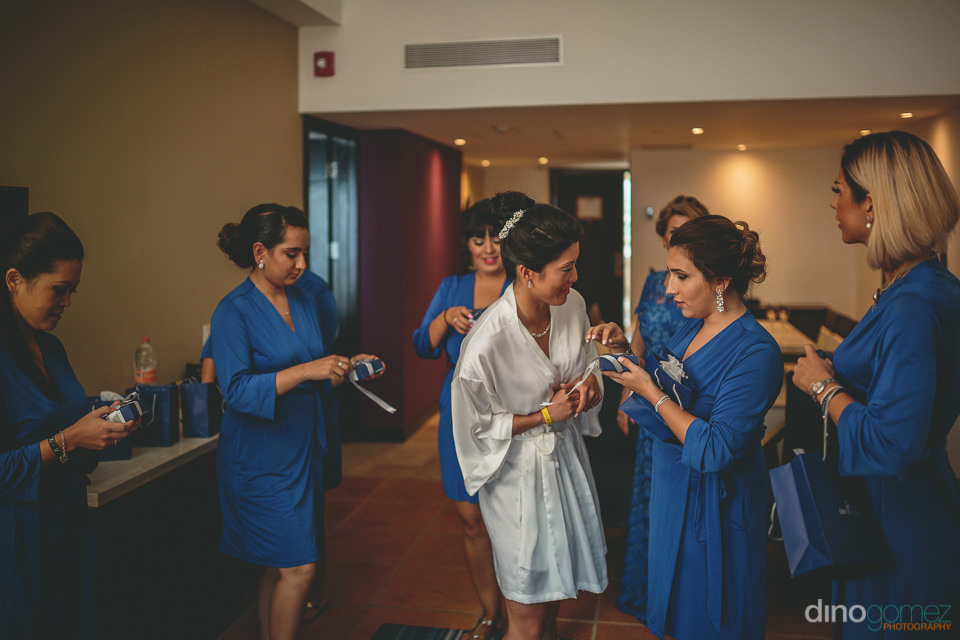 bride gives gifts to bridesmaids before destination wedding on t