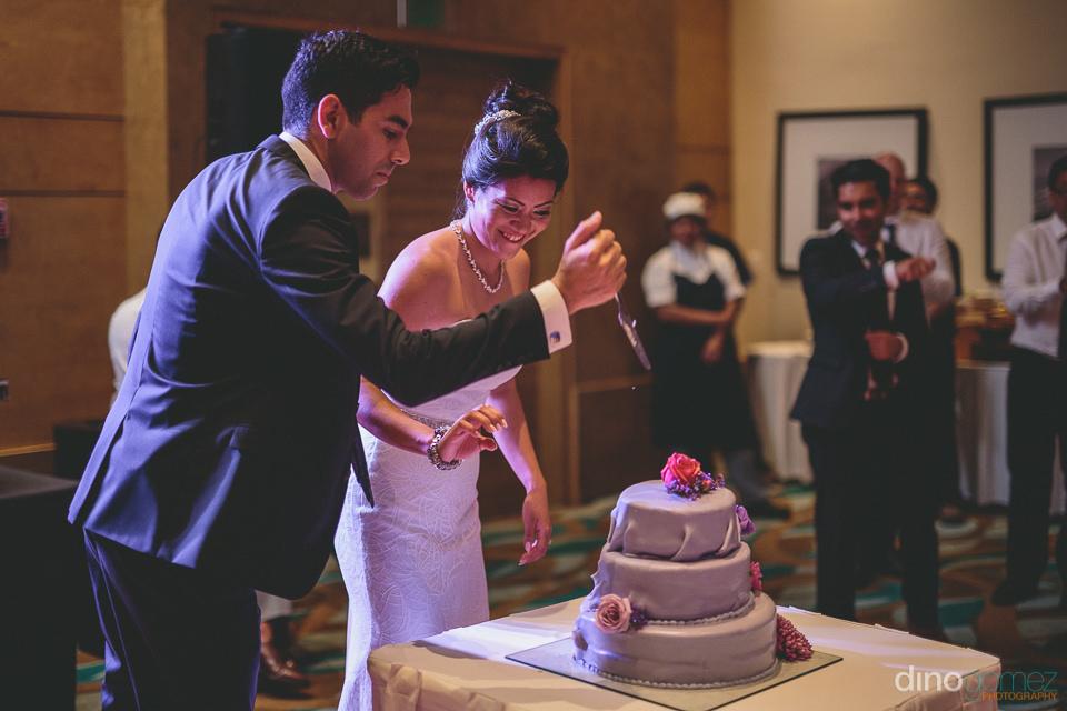groom cuts beautiful velvet wedding cake by cabos best wedding c