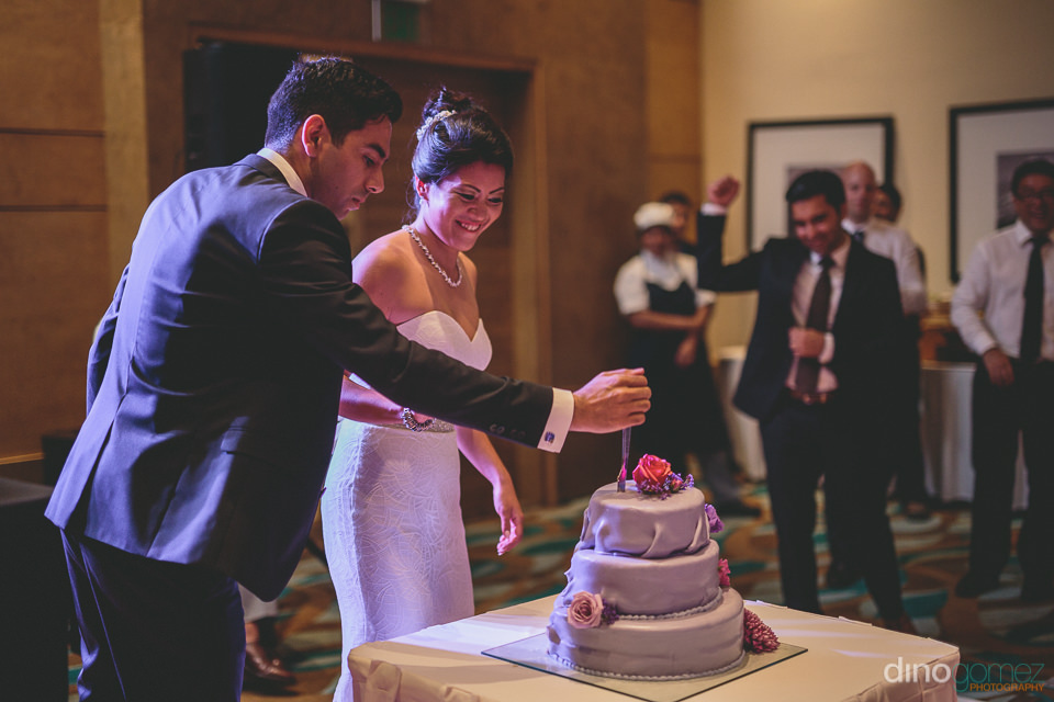 groom makes first cut of wedding cake while guests applaud