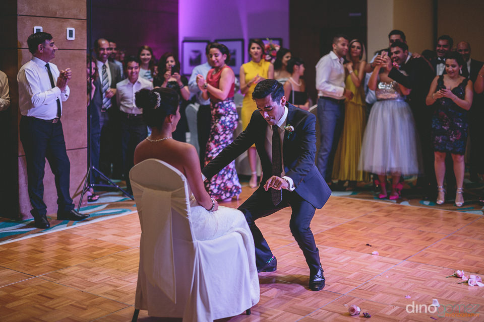 bride sits while groom dances for her on the dance floor of the