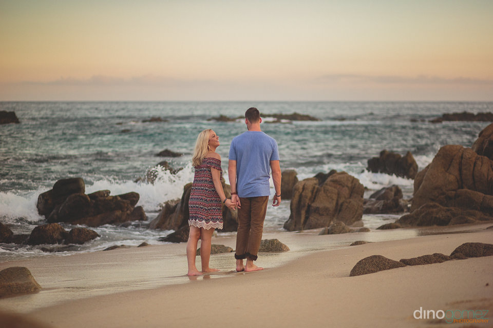 couple walking hand in hand on the beach into the sunset in phot