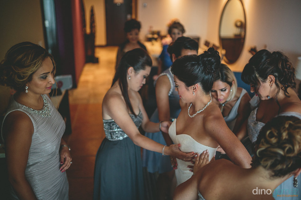 bridesmaids help bride with dress inside the hyatt ziva los cabo