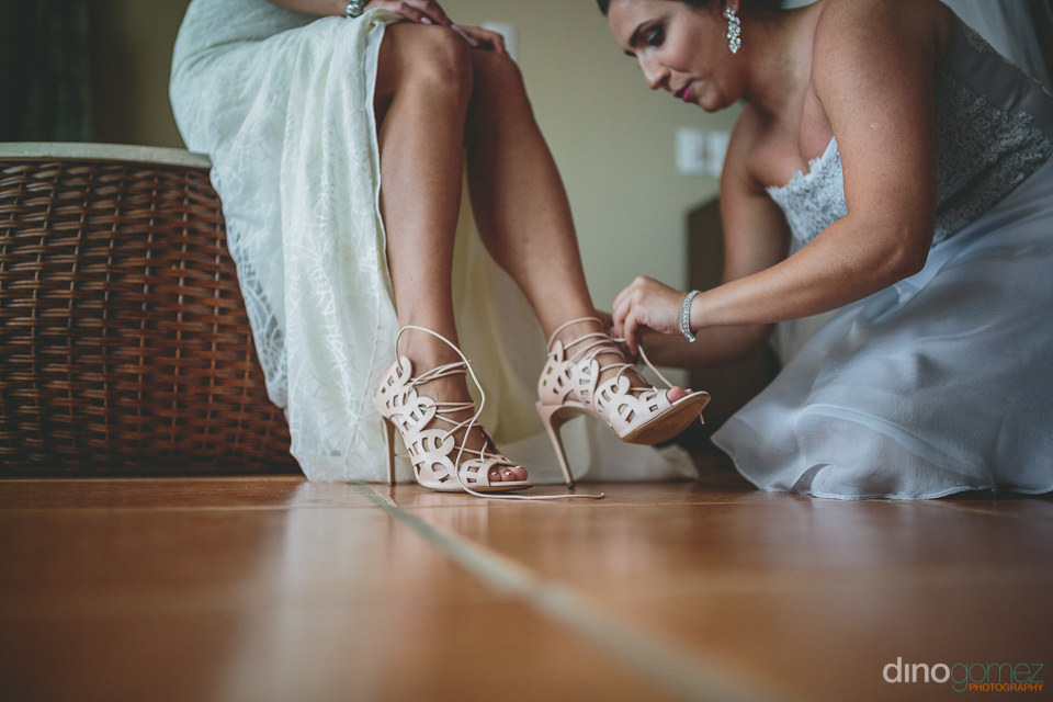 artistic ground level photo of bride putting on her shoes by top