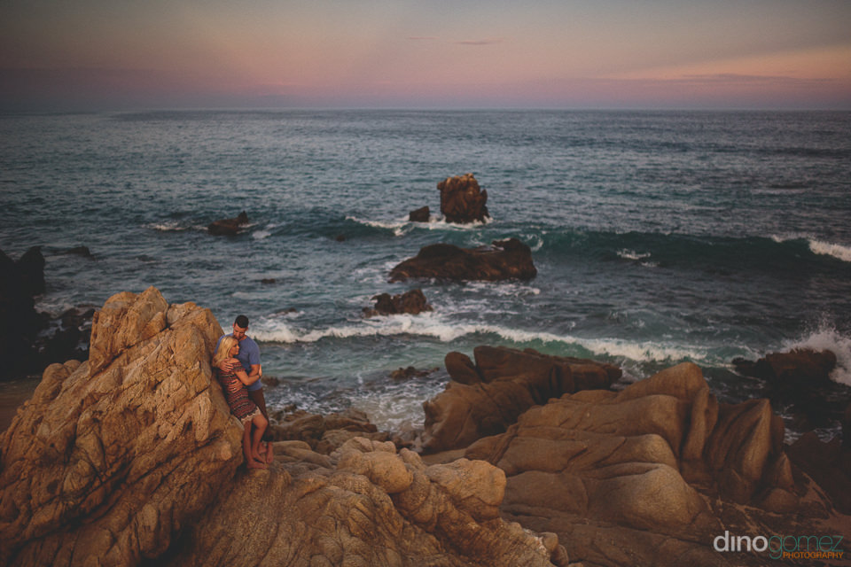 newlyweds stand on beach rocks at sunset in los cabos romantic w