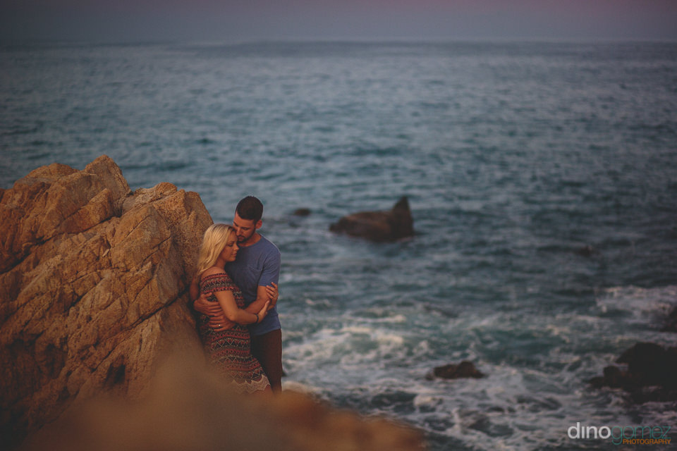 unique wedding photo of newlyweds on beach rocks on secluded cab