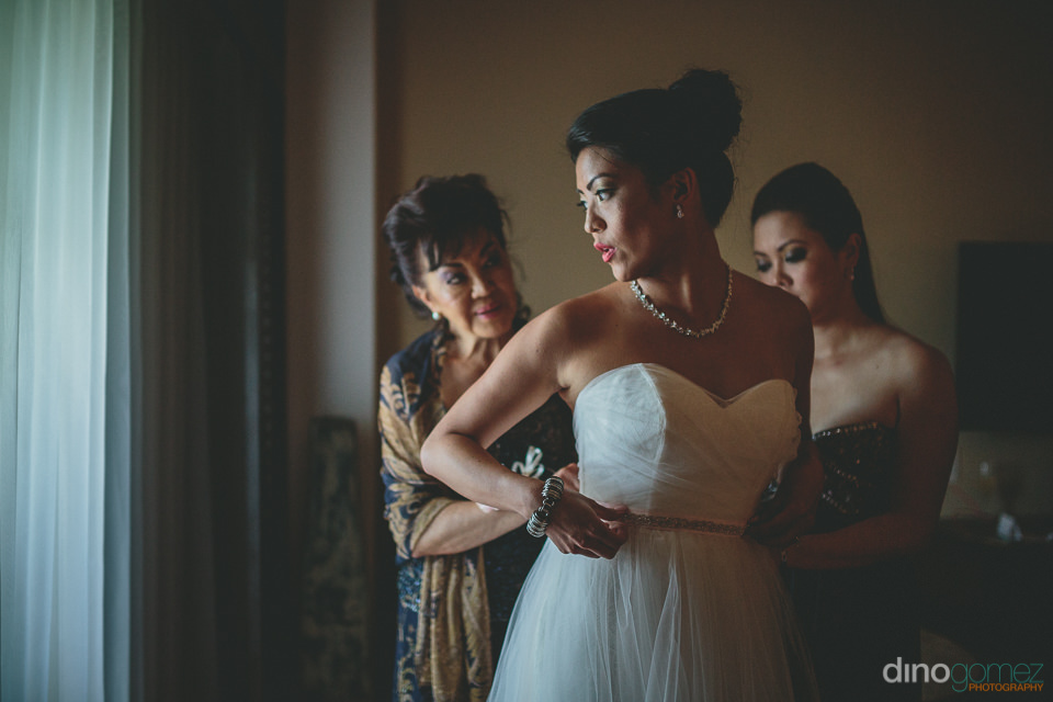 mother of bride helps daughter into wedding dress in loving phot