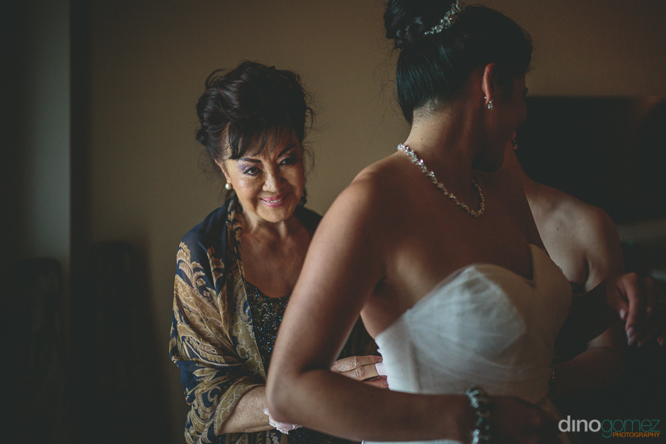 the mother of the bride smiles as she ties up her daughters wedd