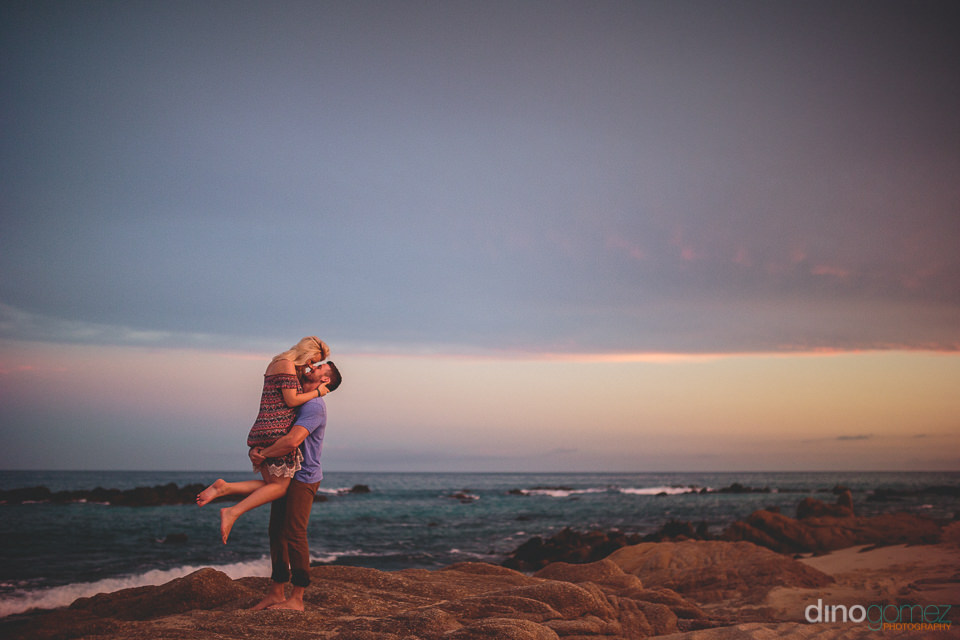 husband lifts up bride in his arms as they kiss on the beach in