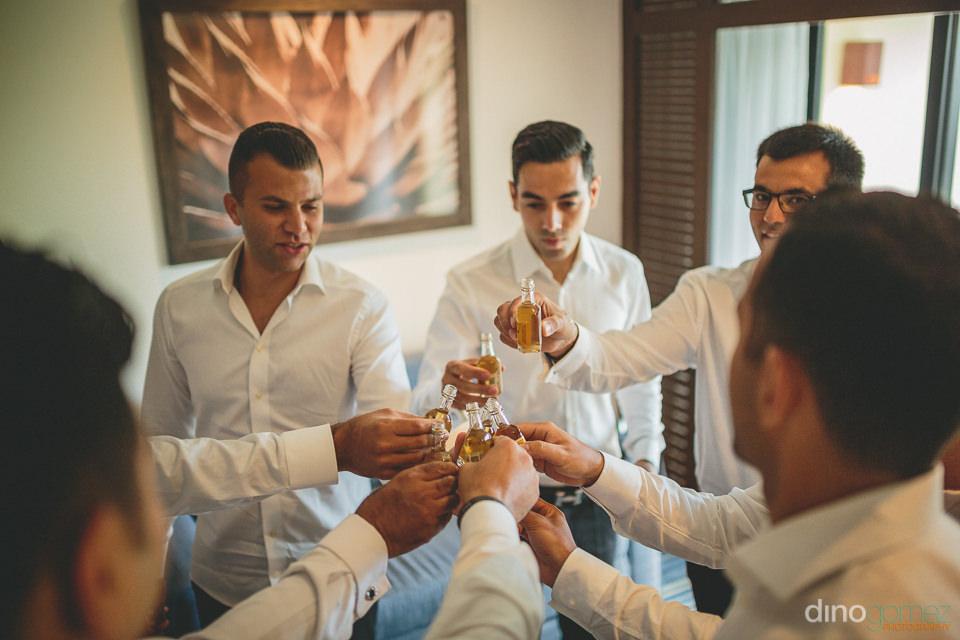 groom groomsmen drink tequila before destination wedding photogr