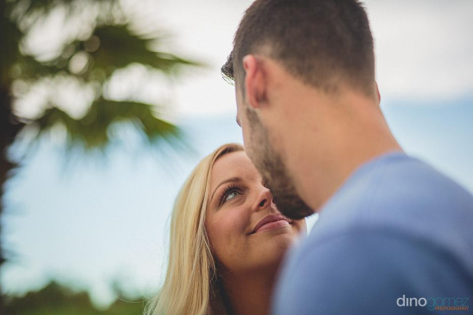 blonde bride smiles at groom under blue sky in romantic wedding