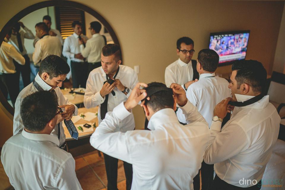 groom and groomsmen tie their ties in their hotel room before th