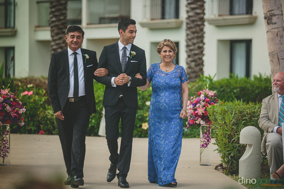 father and mother walk son down the aisle at outdoor beach weddi