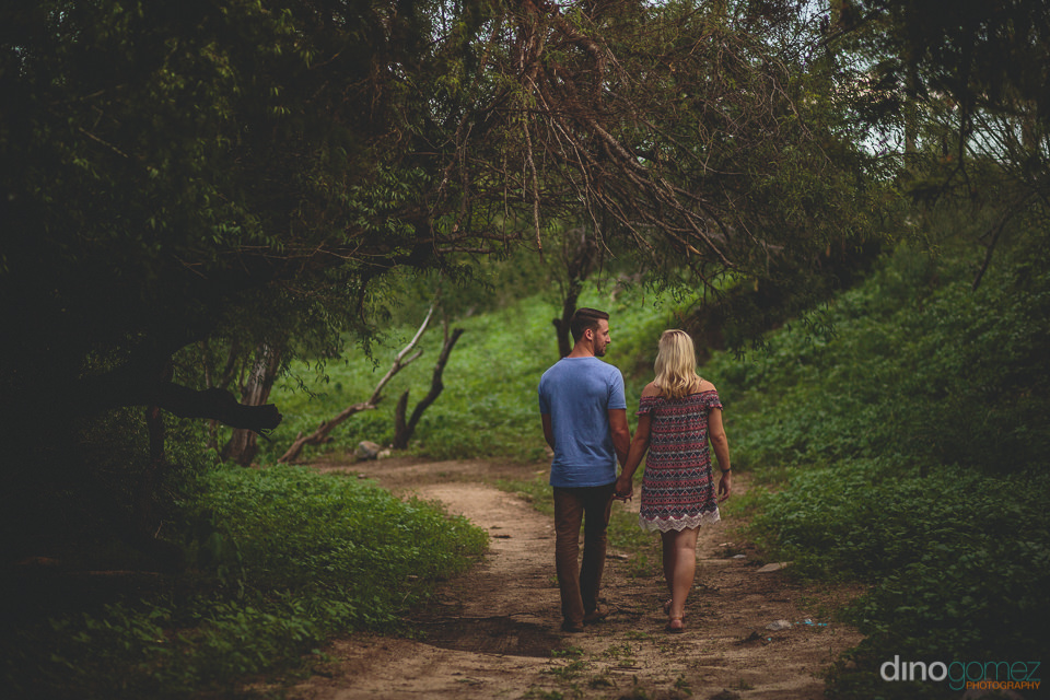 young newlywed couple walk hand in hand down lush green forest p