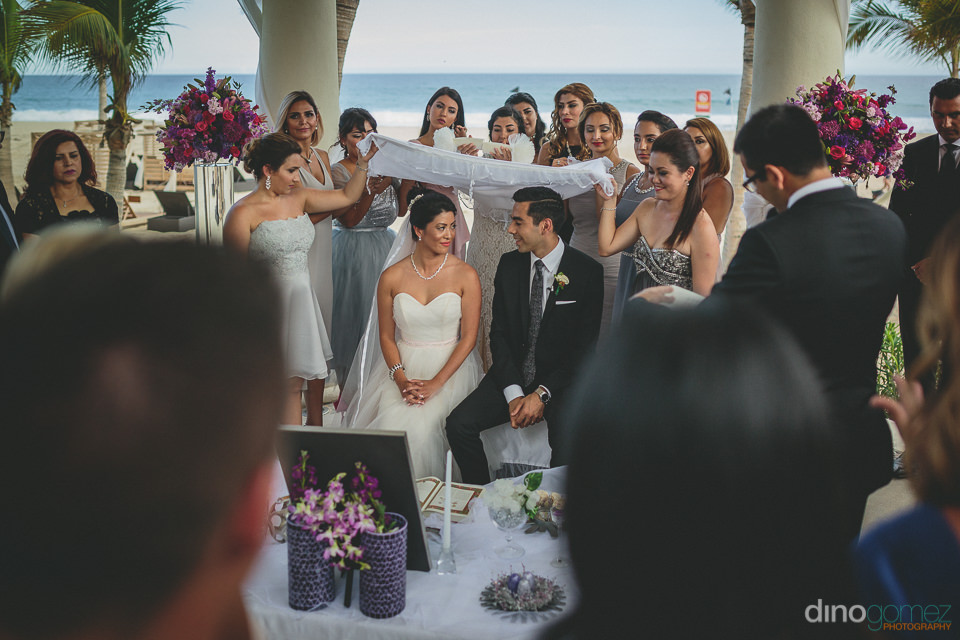 young couple sitting at wedding altar on the beach in mexico in