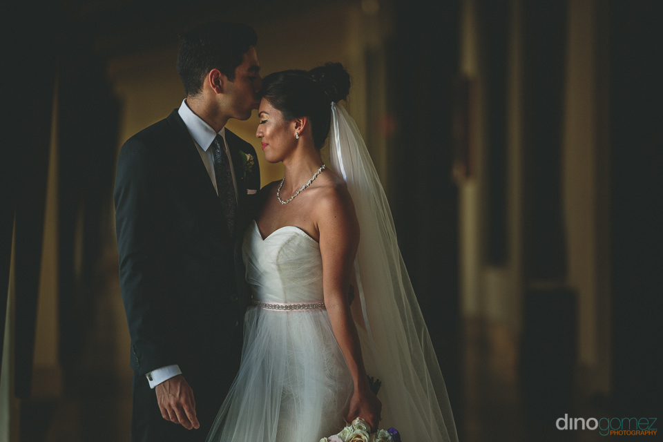 groom kissing bride in classic wedding photo by cabos best photo