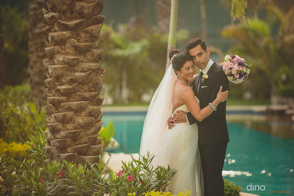 newlyweds embrace by pool at luxury resort during destination we