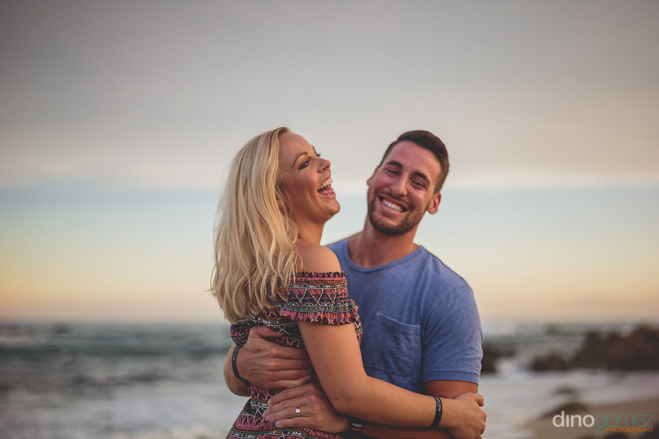 young couple laugh while holding each other on the beach in cabo