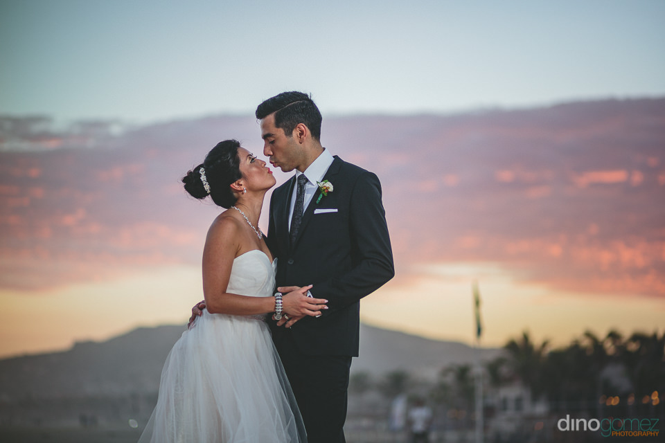 newlyweds kiss as sun sets in the background photo by dino gomez