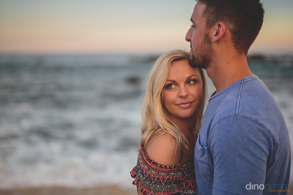 attractive young couple stand close together on the beach at sun