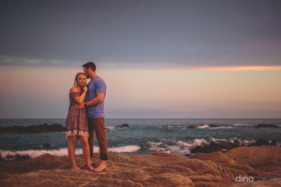 couple stand by ocean at sunset with beautiful sky and ocean beh