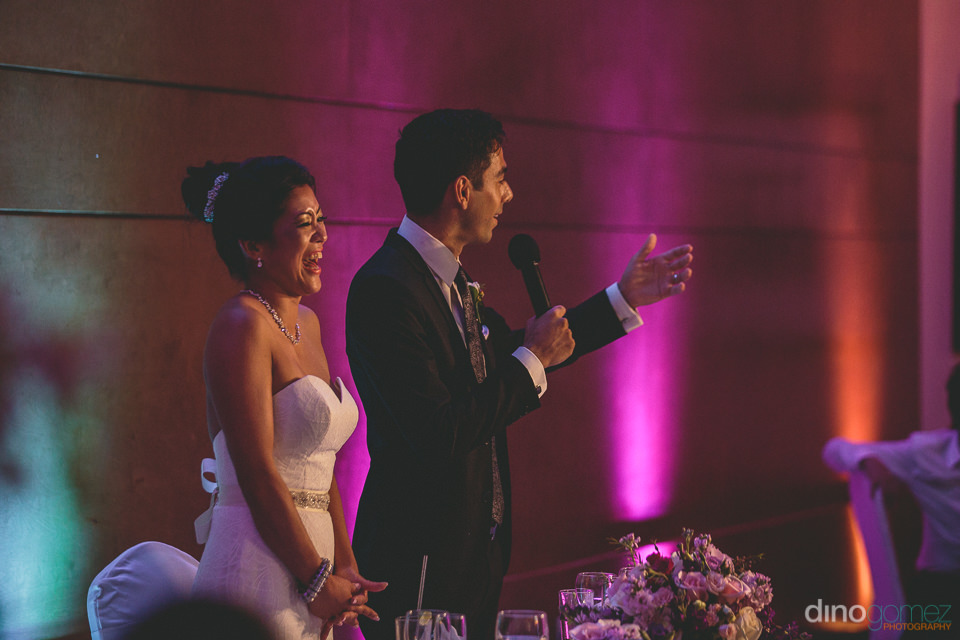 groom gives speech at wedding dinner next to his bride