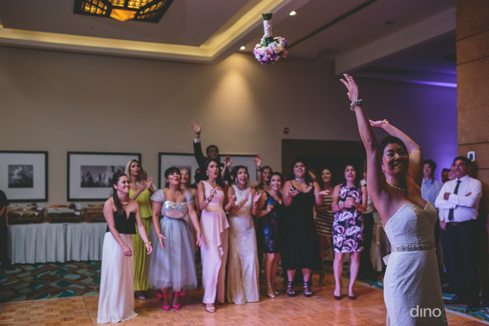 the bride throws the bridal bouquet as her friends stand behind