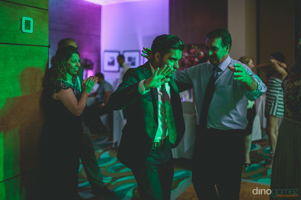 wedding guests illuminated in green light on the dance floor in