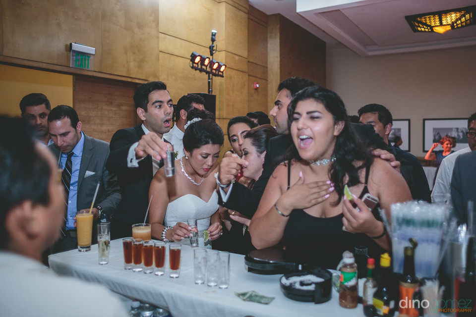 wedding guests stand at bar and drink shots of tequila at cabo w