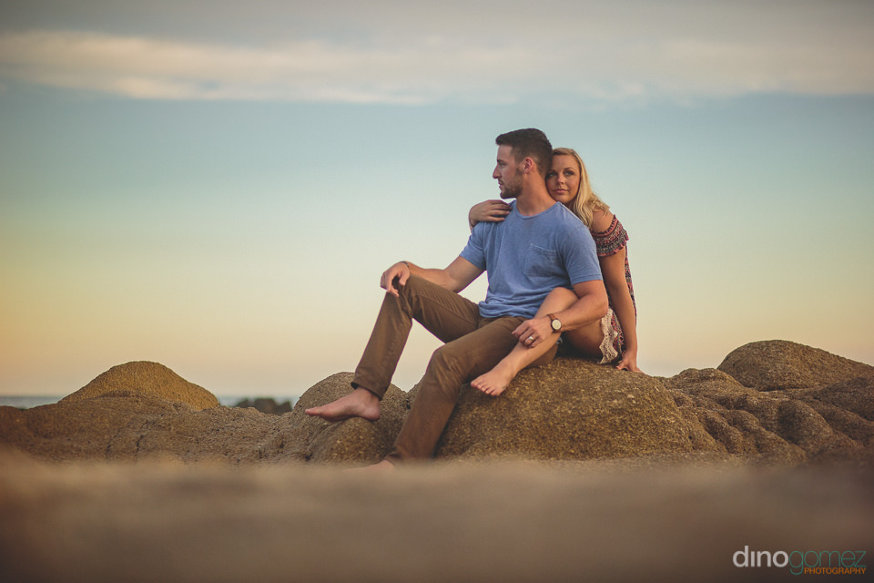 husband and wife sitting on beach rock in front of blue sky suns