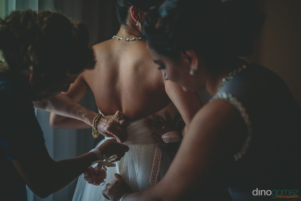 family help to tie up the brides dress in classy wedding photo b