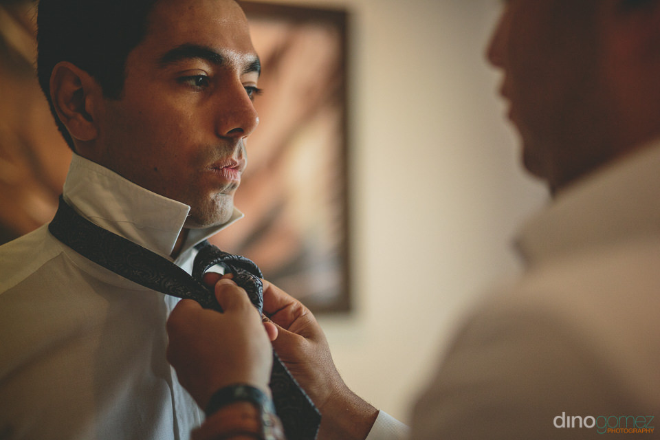 groomsman ties the tie of the groom as they get dressed for the