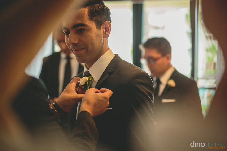groom puts on white rose boutonniere the day of the wedding in c