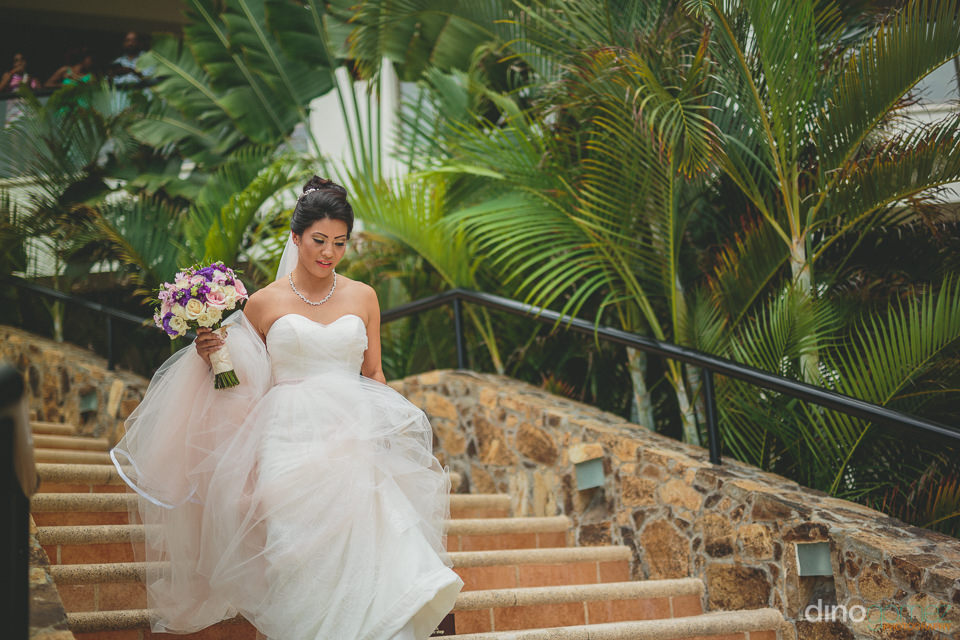 dreamy bride in white dress floats down stairs on way to wedding