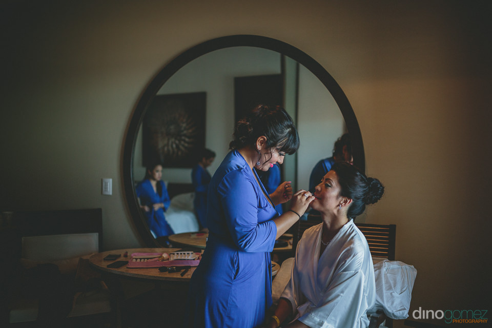 bridesmaid helps bride with makeup in artistic bridal photo by d