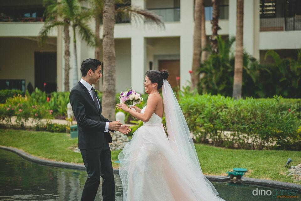 bride sneaks up behind groom and pleasantly surprises him during