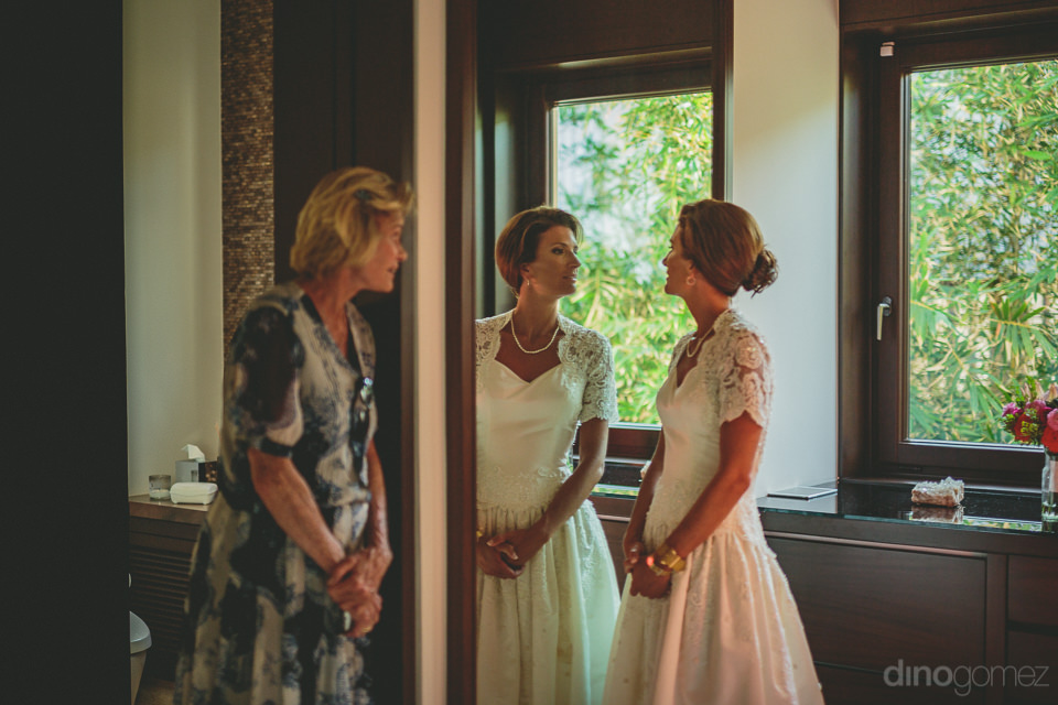 bride looks at herself in the mirror before the wedding as a fam