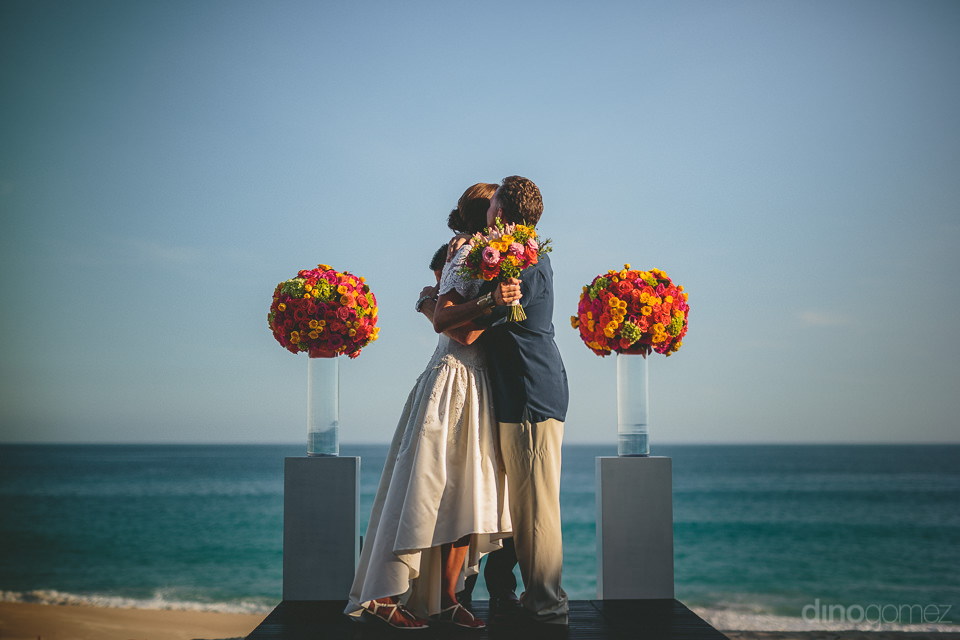 newlyweds hug and kiss at wedding ceremony under perfect blue ca