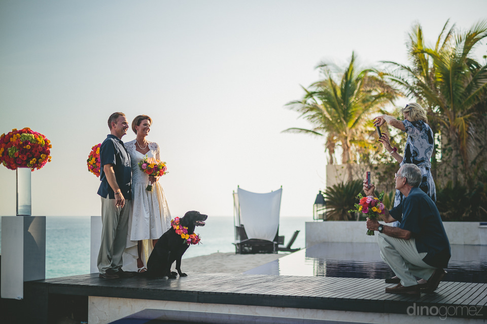 newlyweds and their dog pose for photos at the wedding altar on