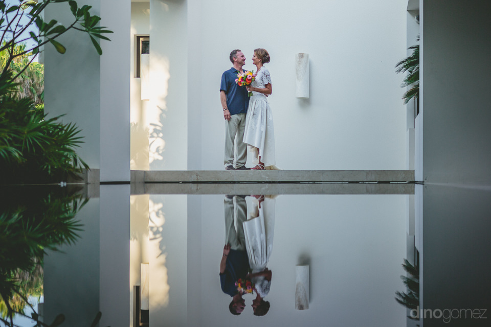 beautiful reflective pool wedding photo of bride and groom by di