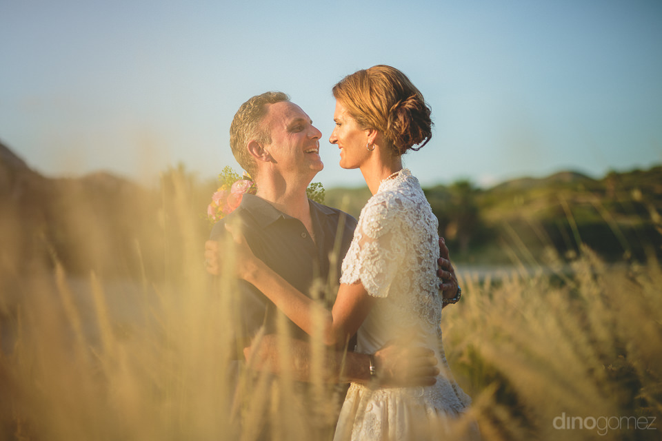 husband and wife newlyweds frolic in tall grass on wedding day