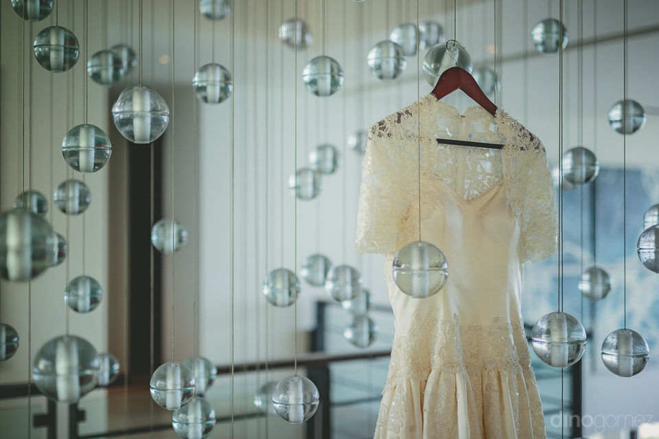 bridal dress hangs next to spherical lights before the wedding a