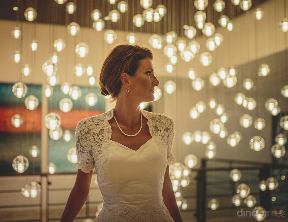bride in white dress sits among dangling white lights in artisti