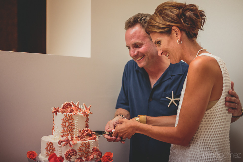 newlyweds cut wedding cake adorned with red and white seashells