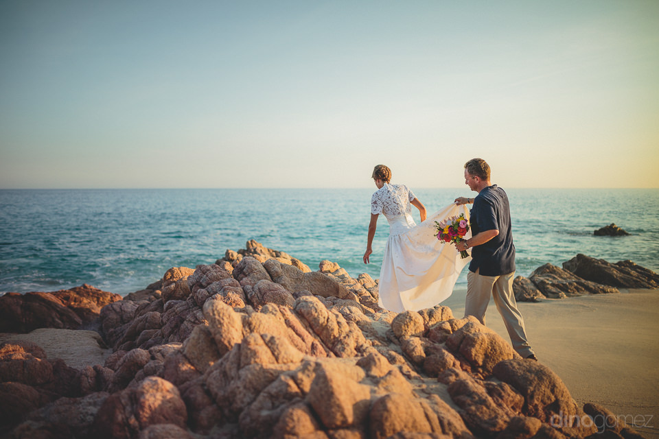 bride in wedding dress climbs on beach rocks in cabo san lucas m