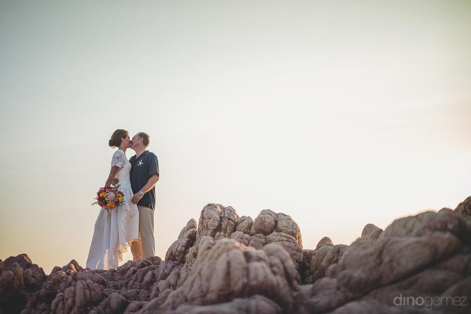 classy and artistic wedding photo of newlyweds atop beach rocks