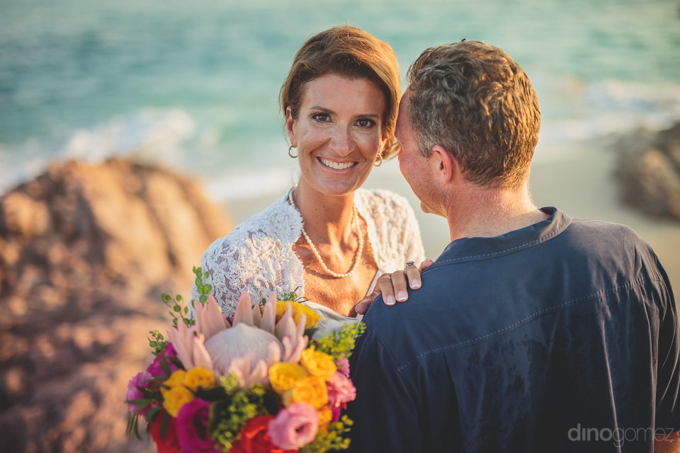 bride smiles at camera while groom looks out over the ocean in w